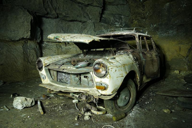 Voiture abandonnée dans une ancienne carrière de pierre